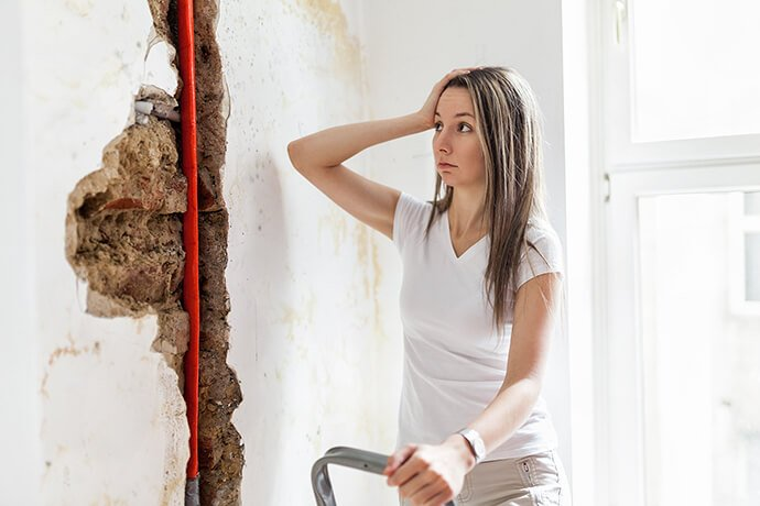 A woman stressing out about a burst pipe.